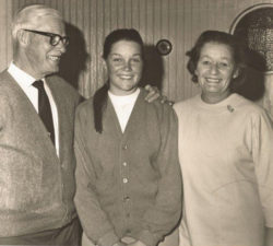 Younger Sally Little standing with her parents