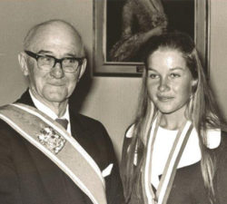 Younger Sally Little standing next to a prestigious man with a award around her neck