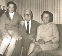 Younger Sally Little sitting with her parents on the couch