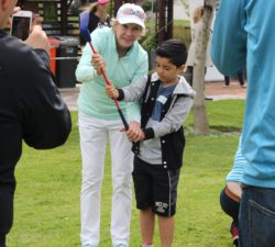Sally Little posing with a kid while holding his club