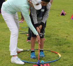 Sally Little helping a kid how to drive the ball by guiding his club
