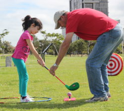 Instructor helping a child to hit the ball to the target