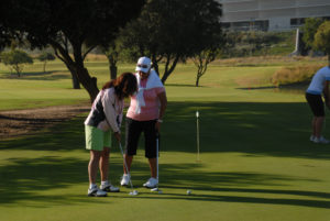 Elder instructor helping women to putt