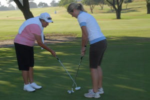 Elder instructor helping women with golf club positioning