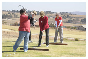 Women in red shirts practicing their golf swing